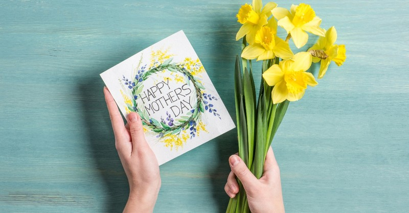 hands holding mothers day card and flowers