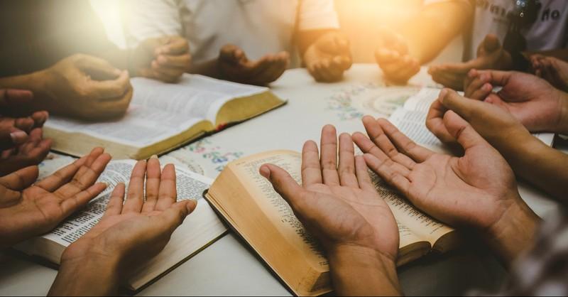 Hands held upward in worship on Bibles
