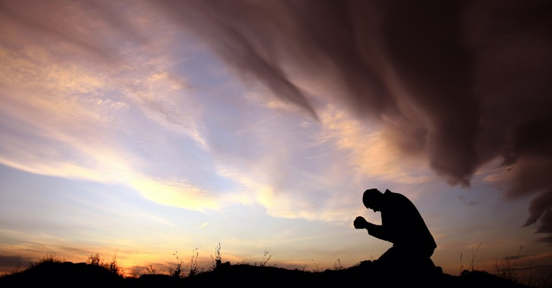 silhouette of man praying outside at dusk in a field, how do we die to self