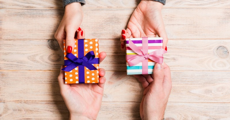 Two people exchanging small gifts