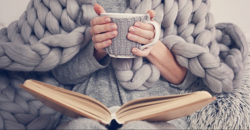 Woman covered in a blanket with a coffee mug