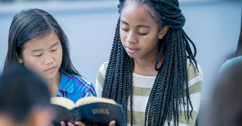 An older girl shares the Bible with a younger girl