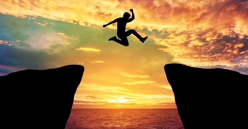 Man leaping over a cliff
