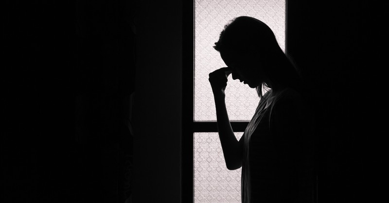 silhouette of woman in dark room looking distressed, prayer against attacks of enemy