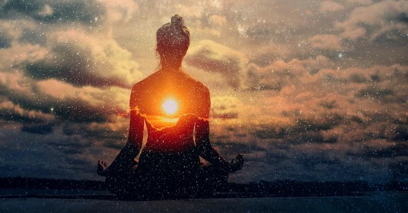 Woman meditating in the galaxy