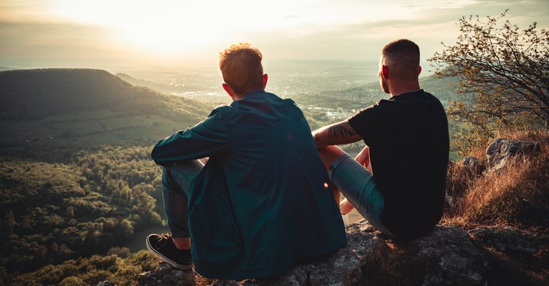 Two men sitting on a cliff looking at the sunrise