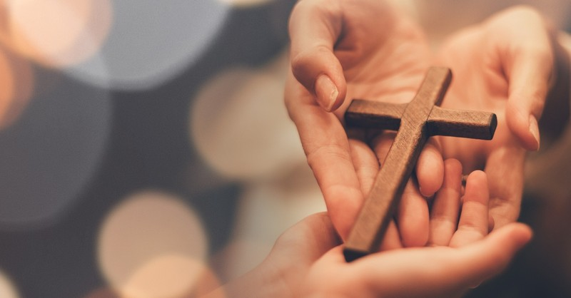 hands holding out cross to smaller hands, how to leave a legacy of faith