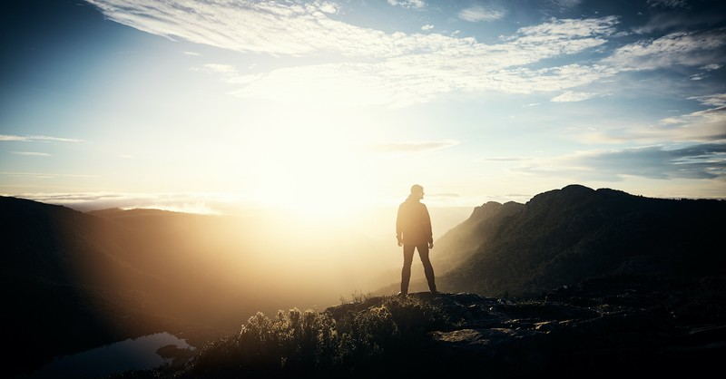 man standing on mountain side looking around at nature, God whispers to Elijah