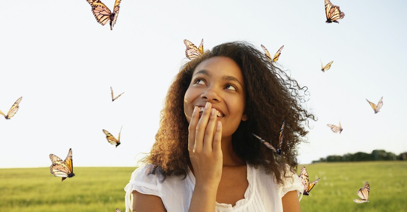 happy woman standing outside surrounded by butterflies, new creation in Christ