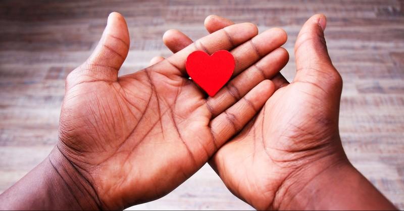 Hands holding a paper heart