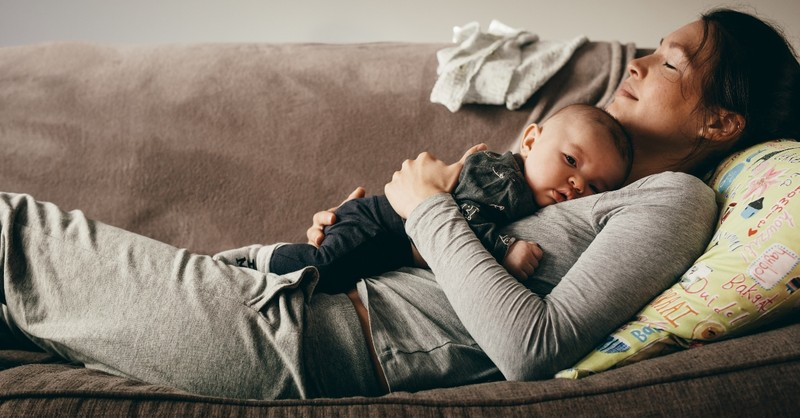 mother sleeping resting with baby on couch, parenting books that won't cause mom guilt