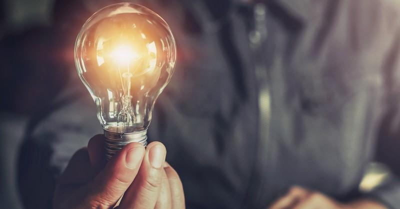 man holding a lightbulb, let your light shine