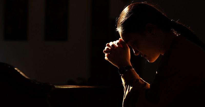 Woman praying in the dark