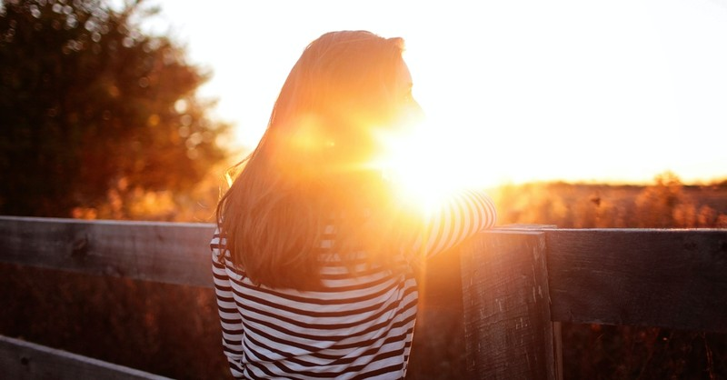 woman standing at fence looking at sunlight, prayer for deep inner healing