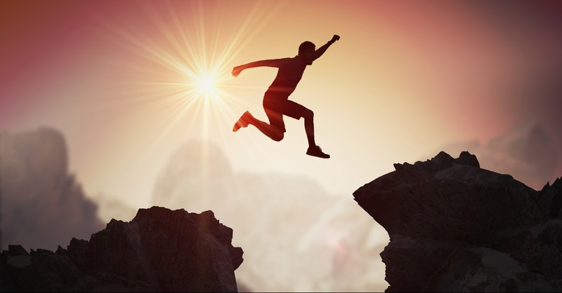 Man jumping across the cliff
