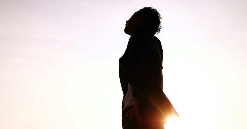silhouette of man looking up and thinking outside in bright sky