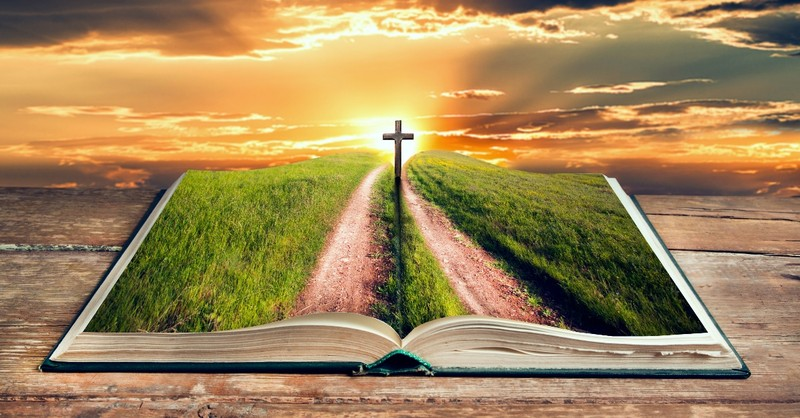 The Bible open with the view of the cross on Calvary