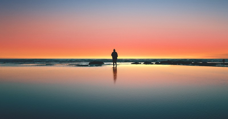 man standing on shore at night under colorful sky alone
