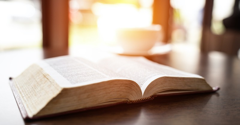 open Bible on table with bright background, what is the meaning of parables