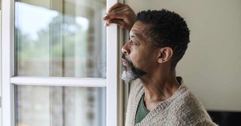 older man standing by open window and looking out, patience of Job