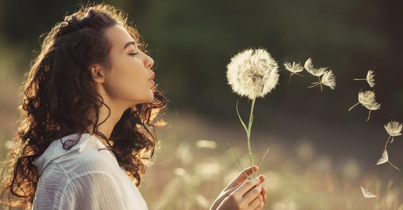 young woman blowing dandelion in field