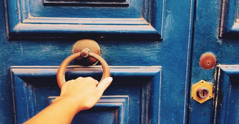 woman's hand pulling door handle on closed locked door, depart from me