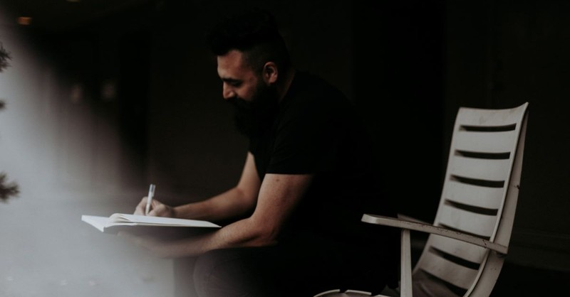 man writing journal journaling sitting all black smiling focused