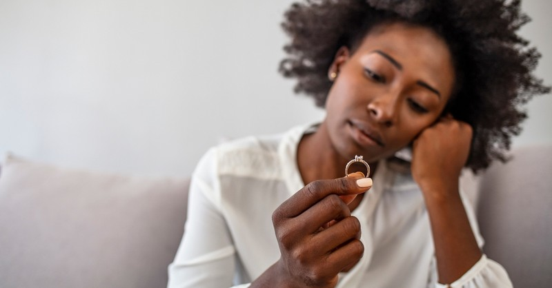 woman holding looking at engagement ring thinking, long engagement