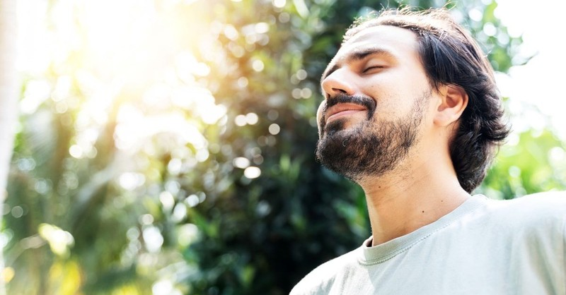 man outside nature eyes closed smiling happy content