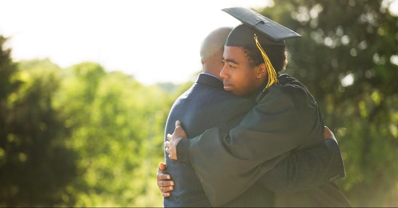 Graduate hugging parent