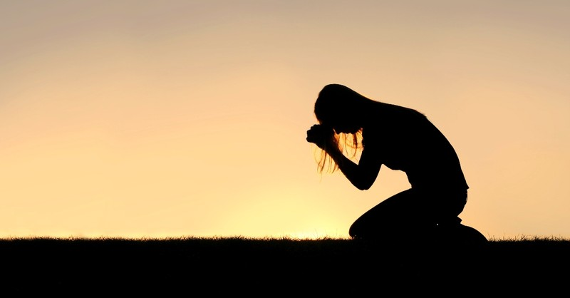 silhouette of woman praying kneeling, power of kneeling in prayer