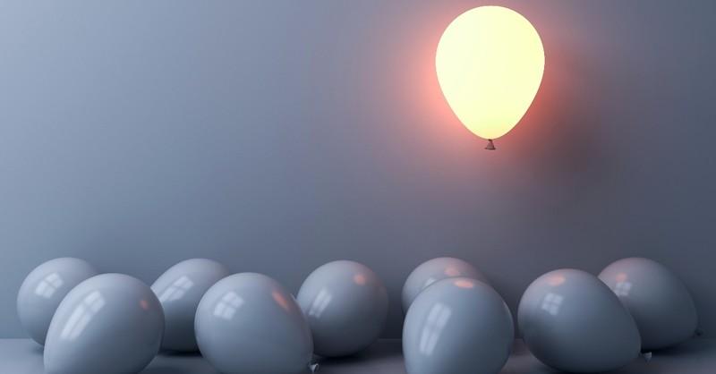 Lighted balloon among gray balloons