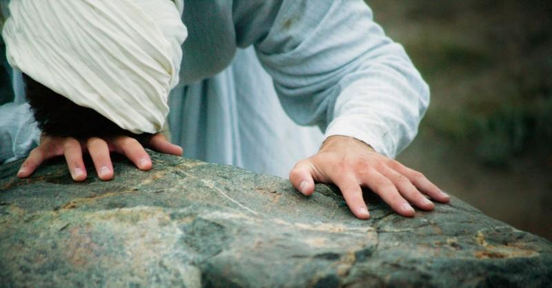 Woman kneeling on a rock praying