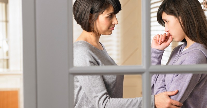 caring mom talking with teen looking anxious