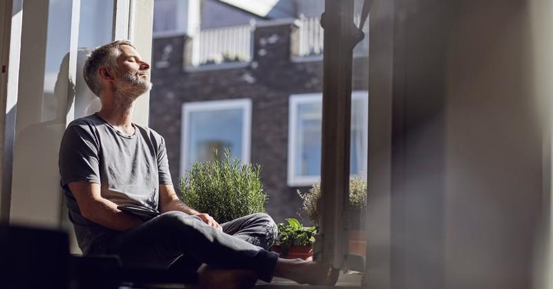 Older man sitting in a window seat relaxing