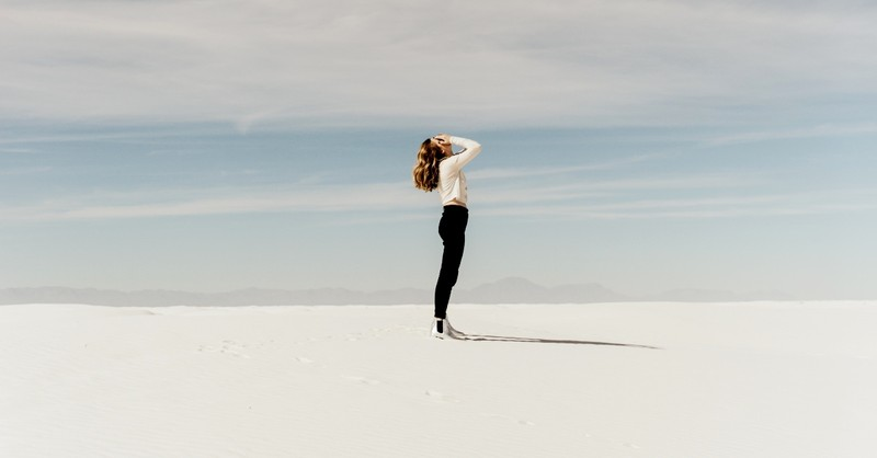 woman standing in white sand desert alone looking up