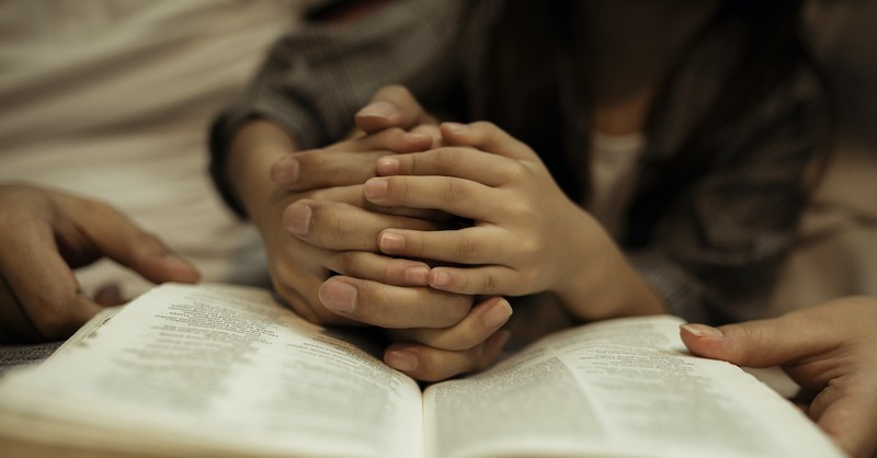 parent and child with prayer hands on open Bible
