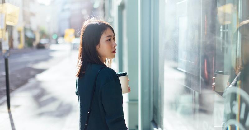 woman looking into glass store window, envy vs. jealousy
