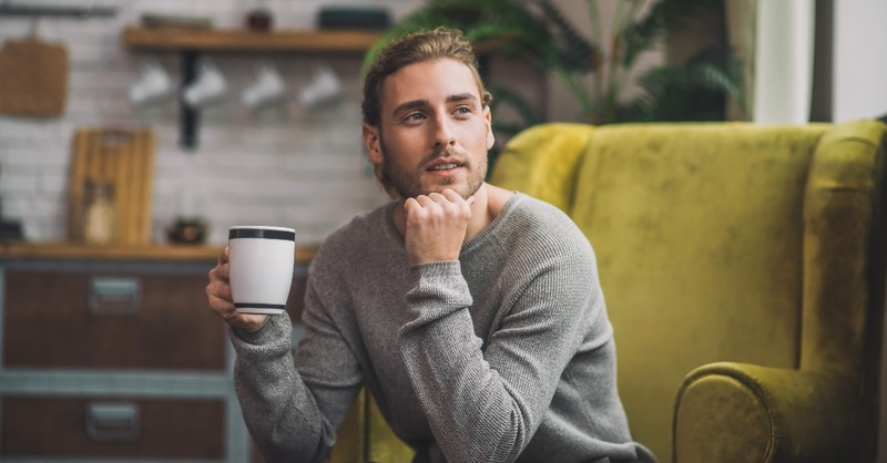 Man contemplating with a cup of coffee