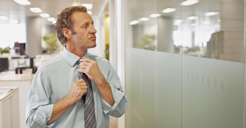 Arrogant man straightening his tie at his office