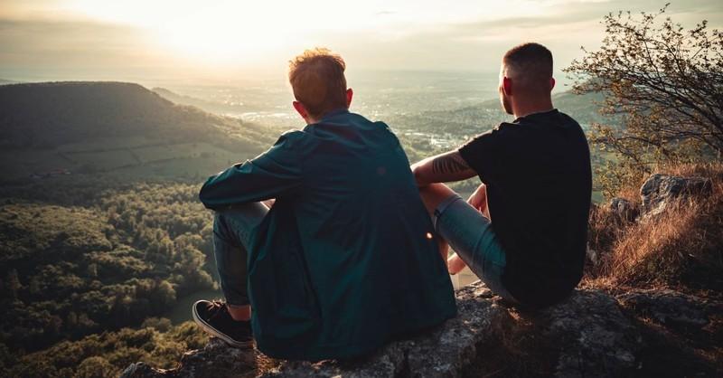 two guy friends sitting on mountain men boys
