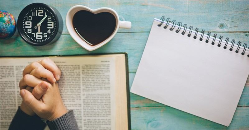 Bible, coffee, notebook, clock, and desk