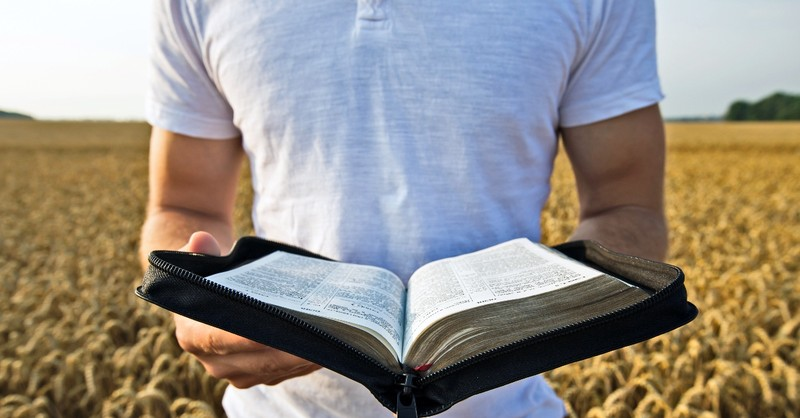 Man holding out a Bible