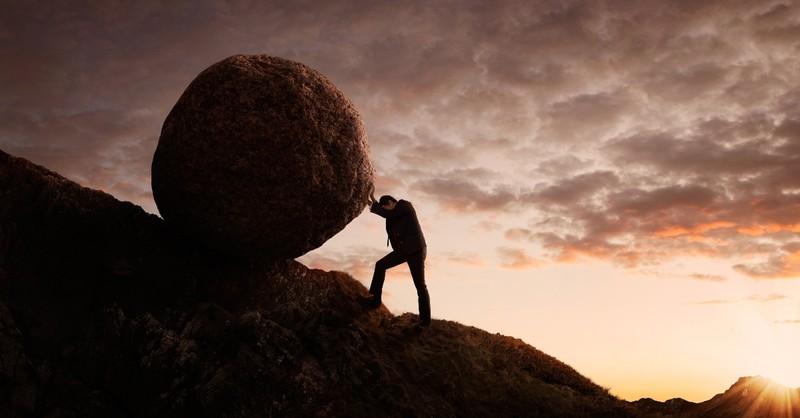 Man pushing a rock up a hill