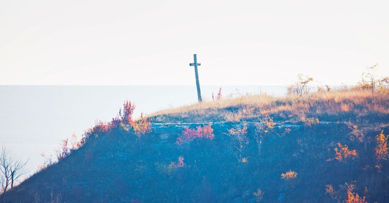 A wooden cross at the end of a cliff