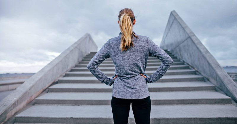 Woman waiting to to run up a set of stairs