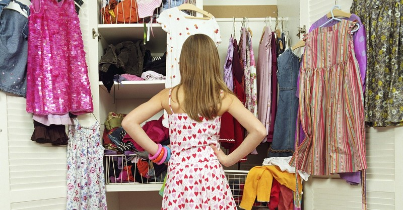 A woman with her back turned chooses what to wear from her closet