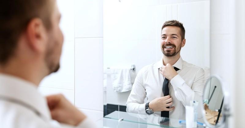 man looking in mirror fixing tie dressed up smiling bathroom getting ready