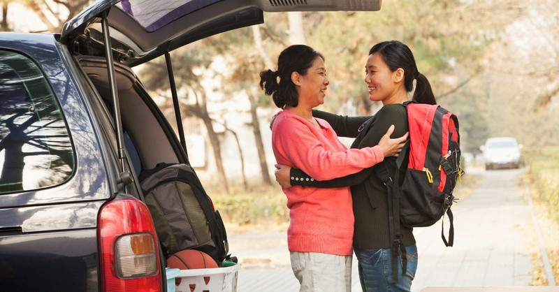 Mother and daughter embracing in front of a packed car