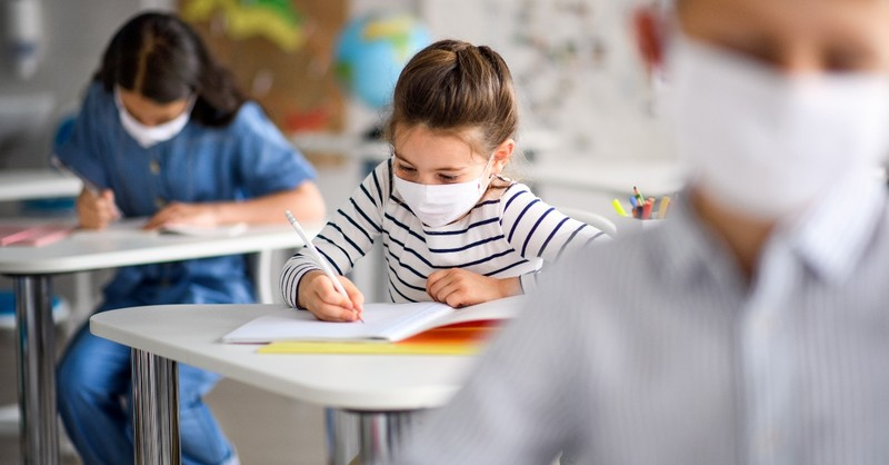 young girl student working at desk in class with mask, back to school prayers